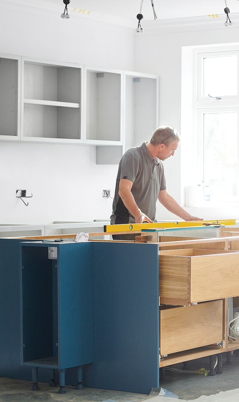 This image shows a man installing a kitchen.
