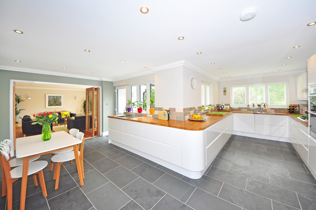 This image shows a white-painted kitchen design with wood materials on the surface of the counters.